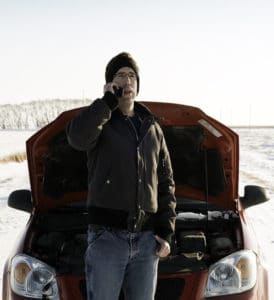 A man calling for help on the side of a snowy road with the hood of his vehicle open